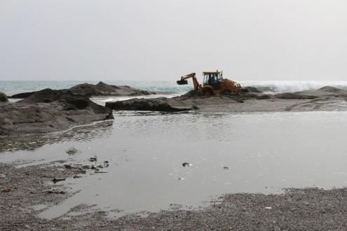 Máquina del Ayuntamiento de MOtril trabajando en la salida de agua en la playa de Poniente (Foto: El Faro)